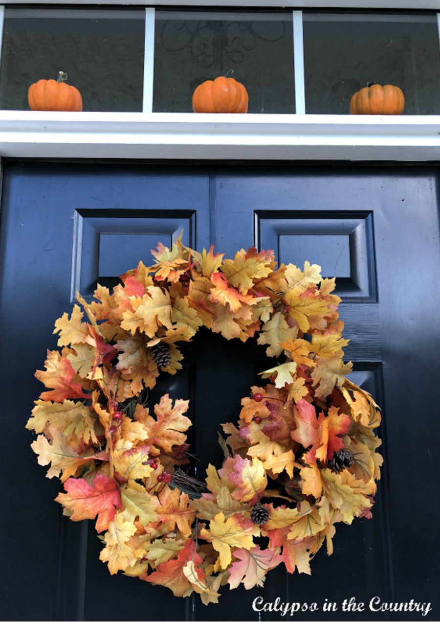 Autumn Porch Decor - Colorful wreath on door with mini pumpkins above